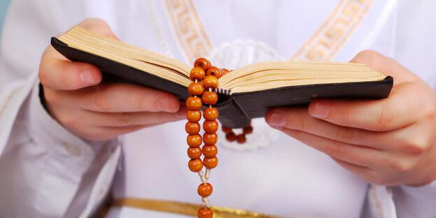 Kommunionkind liest aus Gebetsbuch